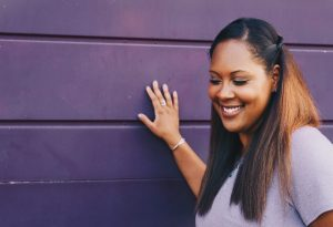 African American Woman Smiling with Hand on wall